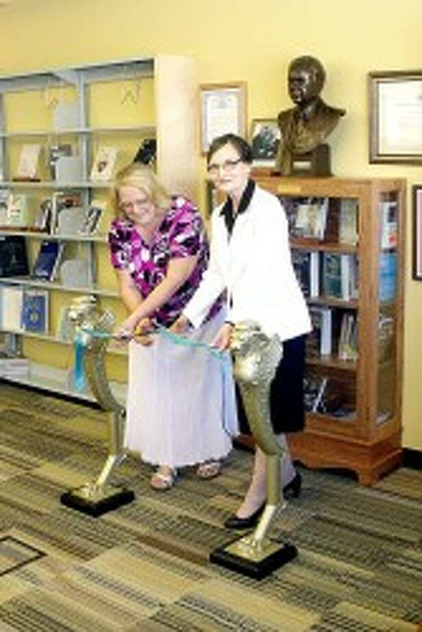 """MAKING IT OFFICIAL: Annette Kirk (left) and library director Mary Ann Lenon cut the ribbon officially opening the display at the Morton Township Library. """"This is a great day, and a great celebration as we dedicate this wonderful display and space to the memory of Russell Kirk,"""" said Lenon. (Pioneer photos/Jim Crees)"""