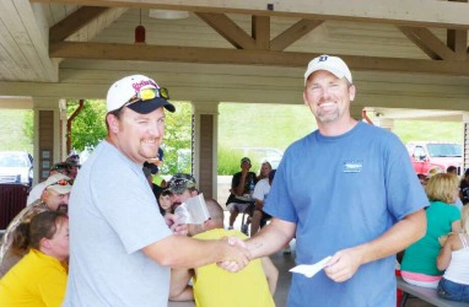 WINNER, WINNER:Tim Johns (right) of the Castaways presents honors to Jason Snyder at last Saturday's awards program. Snyder received the prize for first place in the banquet tournament held that morning. Scott Vinton and Snyder were second in the final Castaway team standings for a combined weight of 51.74 pounds of bass during the summer tournament. (Courtesy photo)