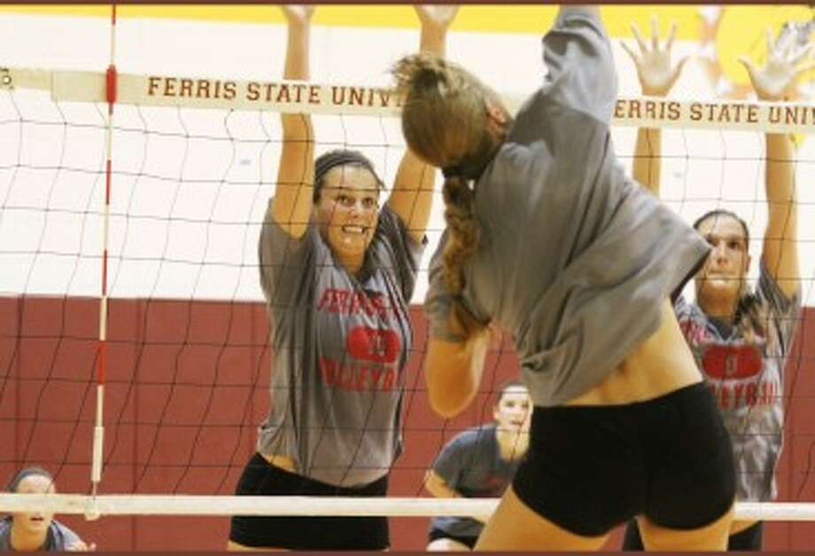 SHOW OF HANDS: Ferris State's Alexis Huntey (left) looks to block a teammate's kill attempt during a recent practice. Huntey joined the FSU volleyball team in the spring after playing last year at George Washington University. (Pioneer photo/Martin Slagter)