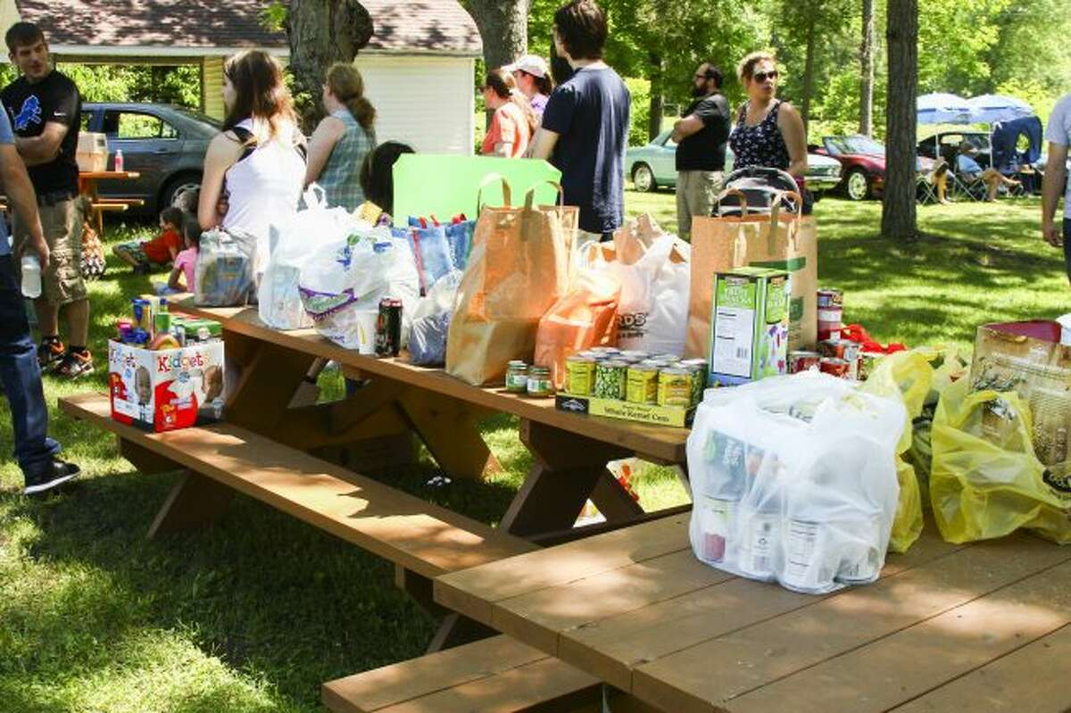 Bags and boxes of food items sit on top of picnic tables at last year's Mecosta-Osceola Food Drive Carnival at Mosaic Park in Hersey. (Pioneer file photos)
