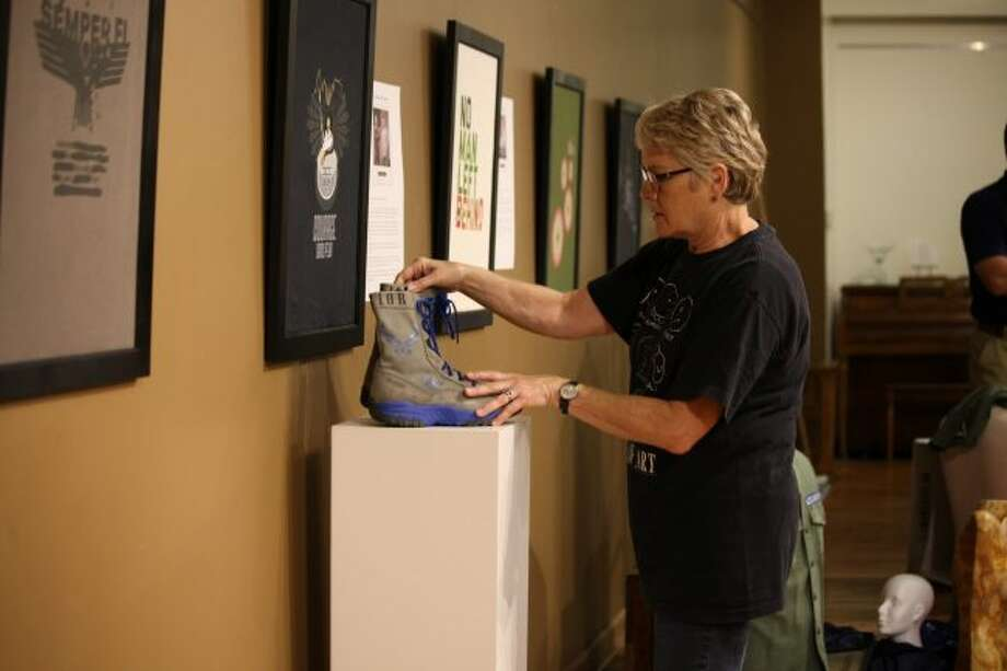 Julie Tilmann, exhibit volunteer, arranges boots on a stand. The boots, as well as designs, uniforms, poems and artwork displayed at Artworks are parts of the Salute to Veterans exhibit series. The exhibit opens Friday, Sept. 29. (Pioneer photos/Meghan Haas)
