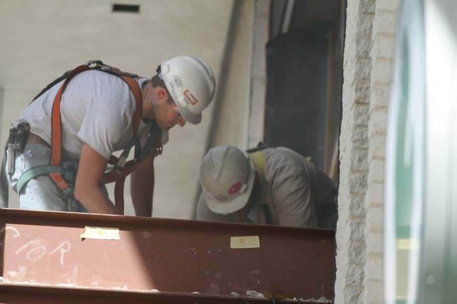 RENOVATION: Crews work changing the front and rear doors of Chemical Bank, located at 125 N. Michigan Ave.