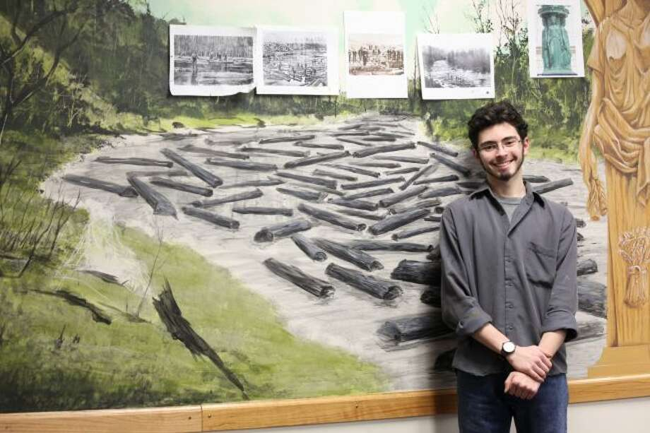 Gordon Mallett has spent approximately 140 hours painting a mural along the back wall of the Big Rapids City Commission chambers. The piece consists of three panels depicting different views from the city, including a logging scene, historic downtown and a park scene. (Pioneer photos/Taylor Fussman)