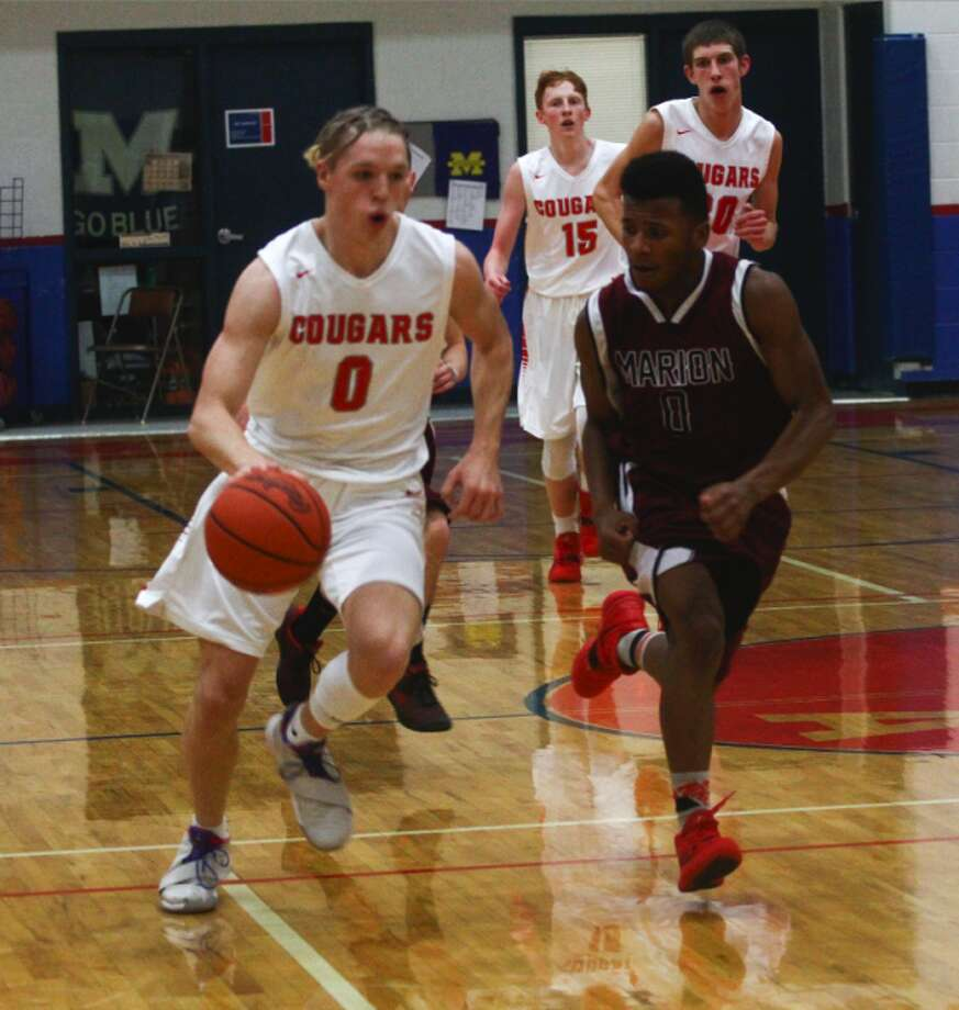 CCA senior Ethan Davis (0) pushes the ball up the floor while being defended by Marion's Ryder Hall (0). (Pioneer photo/Maxwell Harden)