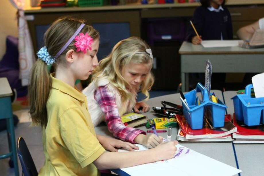 Crossroads Charter Academy elementary students Hannah Porter (front) and Gwen Rumsey work together on a poster during a recent cross-grade buddy meeting. The cross-grade buddy program is part of a new curriculum at CCA. (Pioneer photos/Meghan Gunther-Haas)