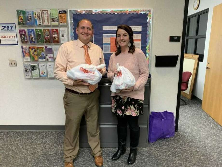 "(From left) Big Rapids High School Assistant Principal Joshua Bull and Kelley Dennert, secretary, hold two ""Angel Bags"" provided by nonprofit organization Angels of Action. The organization recently expanded its weekend food assistance program from mainly elementary and middle schools to include BRHS and Big Rapids Virtual School. (Courtesy photo)"