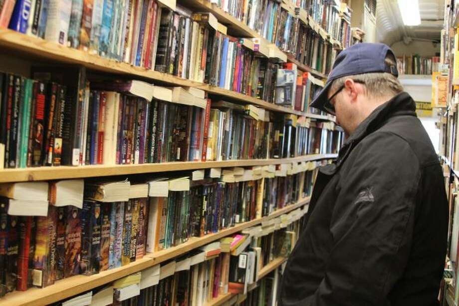 LOOKING: Stan Fortier, of Lake Isabella, looks at a variety of science fiction books on March 25 at the Mecosta Book Gallery. Fortier, like many others, stop by the quaint shop when he drives through the village or wants to see if there are any new books. (Pioneer photos/Brandon Fountain)
