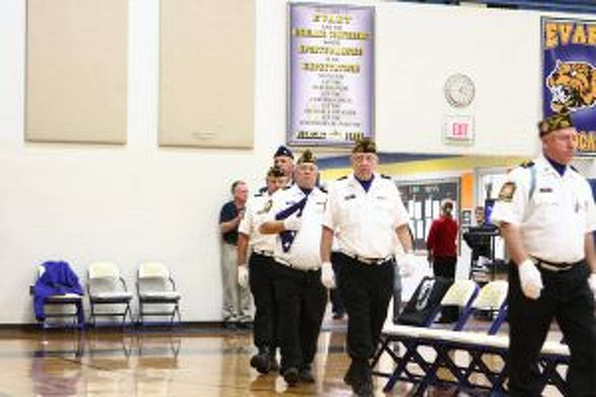 Veterans are welcomed with a standing ovation as they file into the gymnasium at Evart High School during the school's Veterans Day program. Many of the veterans in attendance represent the Evart VFW Post No. 7979.