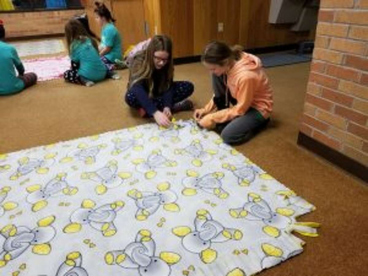 Valerie Krause (left) and Charley Poteracke begin working on their second blanket on Tuesday. After the blankets, they will be donated to Angels of Action and Women's Information Services, Inc.
