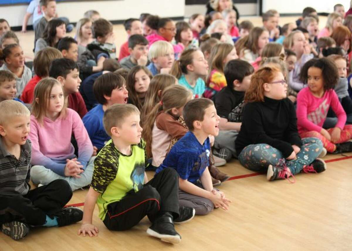 """Second-, third- and fourth-graders from Riverview Elementary School helped act out different parts of """"Patriot Pup,"""" by showing author Elisa Camara their best growl."""