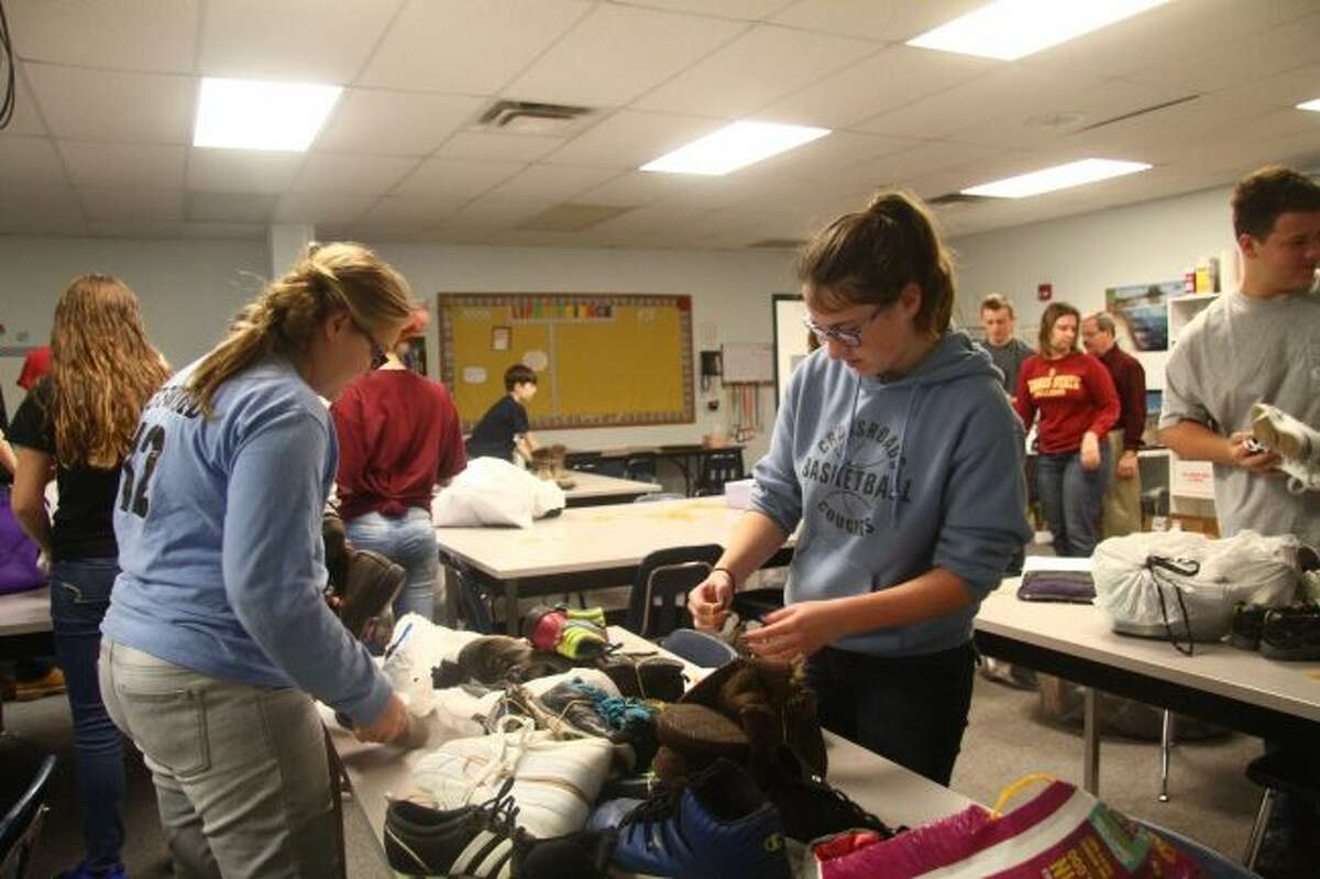 Crossroads Charter Academy eighth-graders Megan Griswold (left) and Allison Dennis work together to sort and band together pairs of shoes for their shoe drive. (Pioneer photos/Meghan Gunther-Haas)