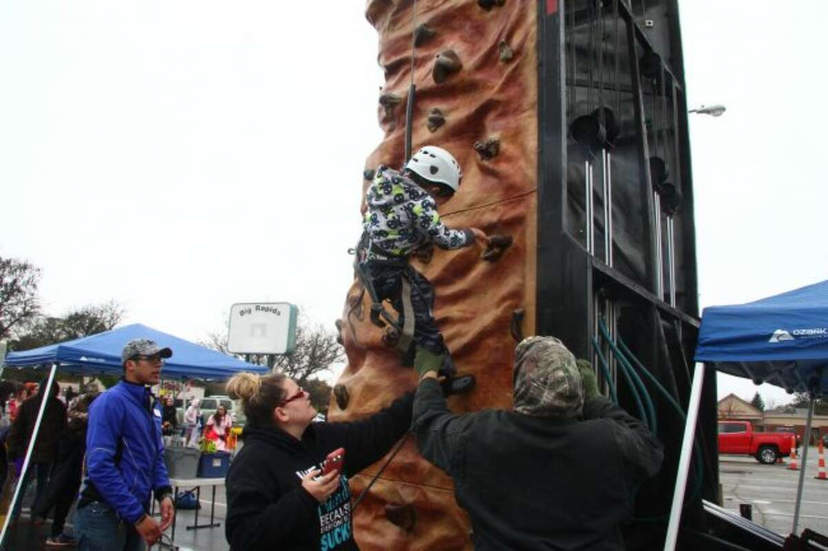 De-Angelo Houston prepares to get down after climbing the rock wall at the Fall Festival.