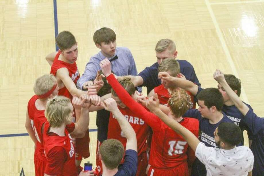 The CCA boys basketball team huddles up during a timeout in Tuesday's D4 state quarterfinal game. (Pioneer photo/Maxwell Harden)