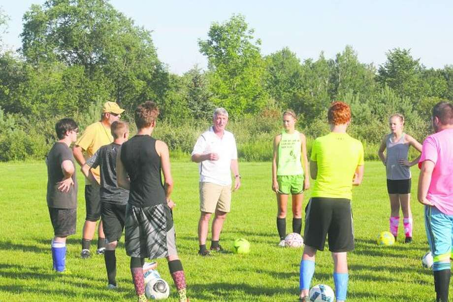 Reed City boys soccer coach Doug Emington (center) works with players on Tuesday during a summer practice. (Pioneer photo/John Raffel)