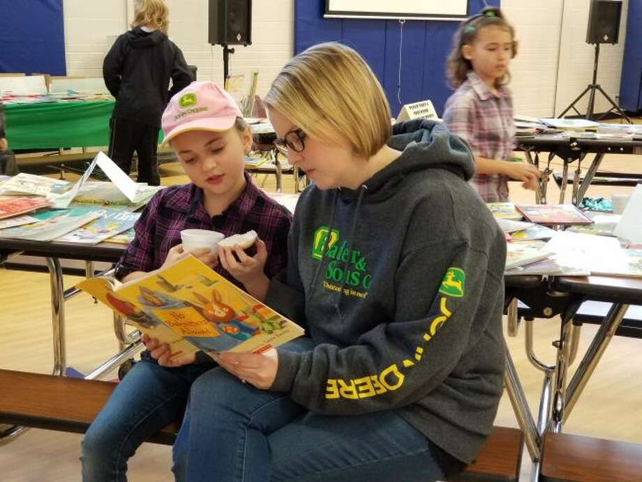 """(From left) Kennadi and Sarah Fuller read """"No Babysitters Allowed,"""" by Amber Stewart, during Bagels and Books in the Barn on Friday at Brookside Elementary. (Videoed) Howard Botma, Big Rapids Community Library story time programmer, entertains students while reading """"Moose on the Loose,"""" by Kathy-jo Wargin. (Pioneer photo/Meghan Gunther-Haas)"""