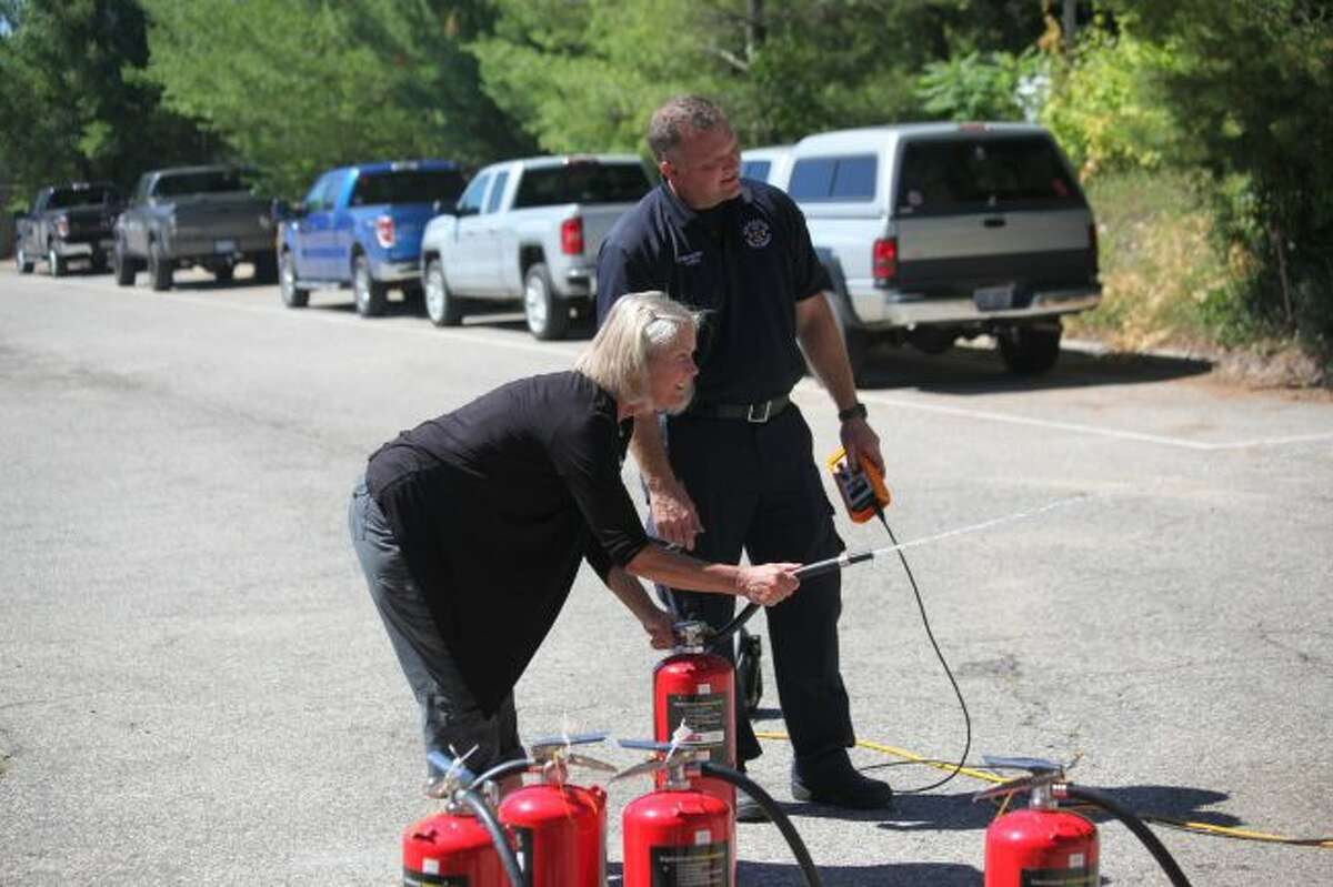 Chris Johnson (front) was assisted by firefighter Russ Bell in extinguishing a kitchen fire during Camp 911 last year. This year's event is scheduled for Wednesday, July 17, at the Big Rapids Department of Public Safety. (Pioneer file photo)