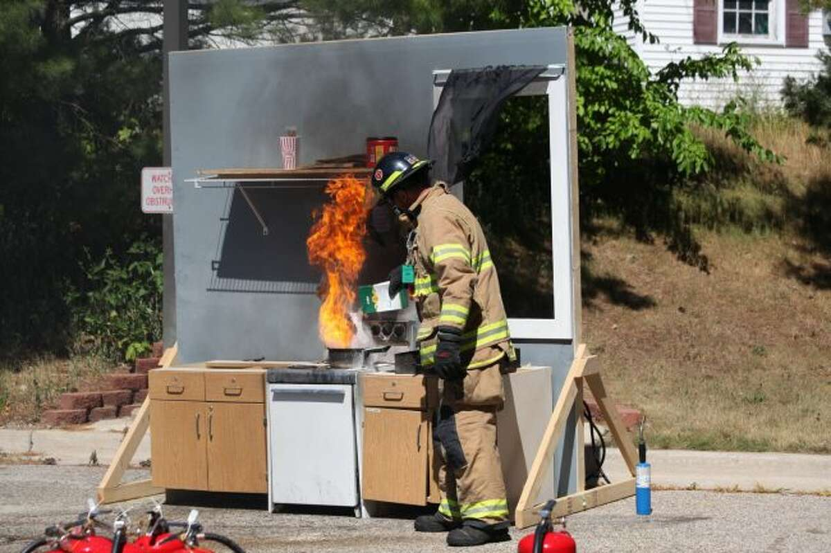 Firefighter Russ Bell demonstrates how to put out a kitchen fire using baking soda during the 2018 Camp 911. Area seniors will learn this skill and many more during this year's annual event. (Pioneer file photo)