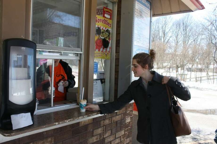 Ferris State University student Amy Bell is pictured purchasing ice cream at State Street Scoops, which opened for the season Monday. (Pioneer photo/Tim Rath)