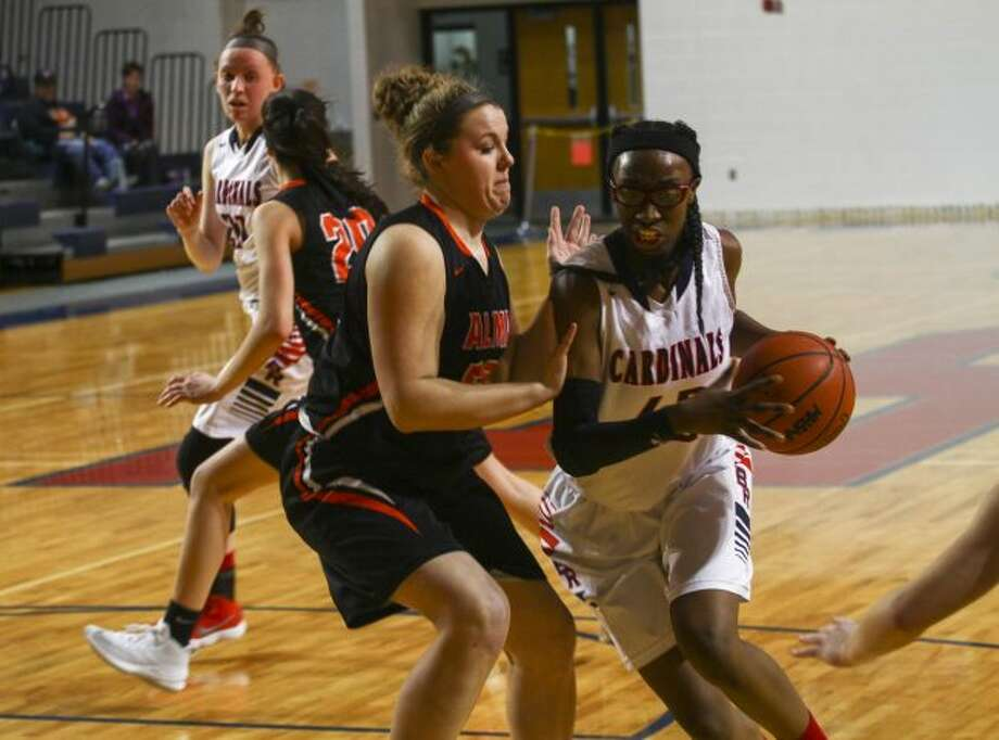 Jayla Strickland (right) drives to the hoop during Monday's district opener against Alma. (Pioneer photo/Maxwell Harden)
