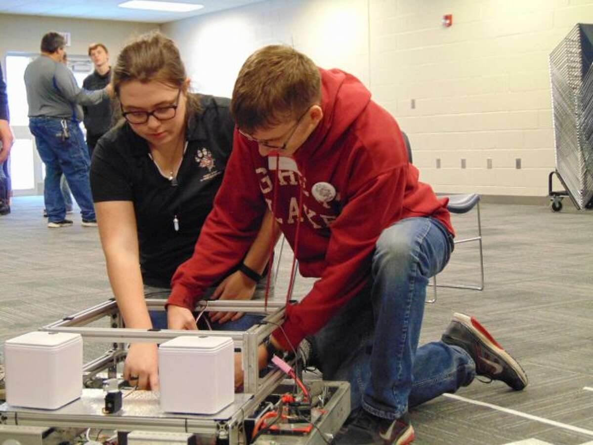 Reed City Area Public School robotics members Sophie VanAntwerp (left) and Connor Williams work together powering on their robot to show how it functions to the Chippewa Hills School District team. (Pioneer photos/Meghan Gunther-Haas)