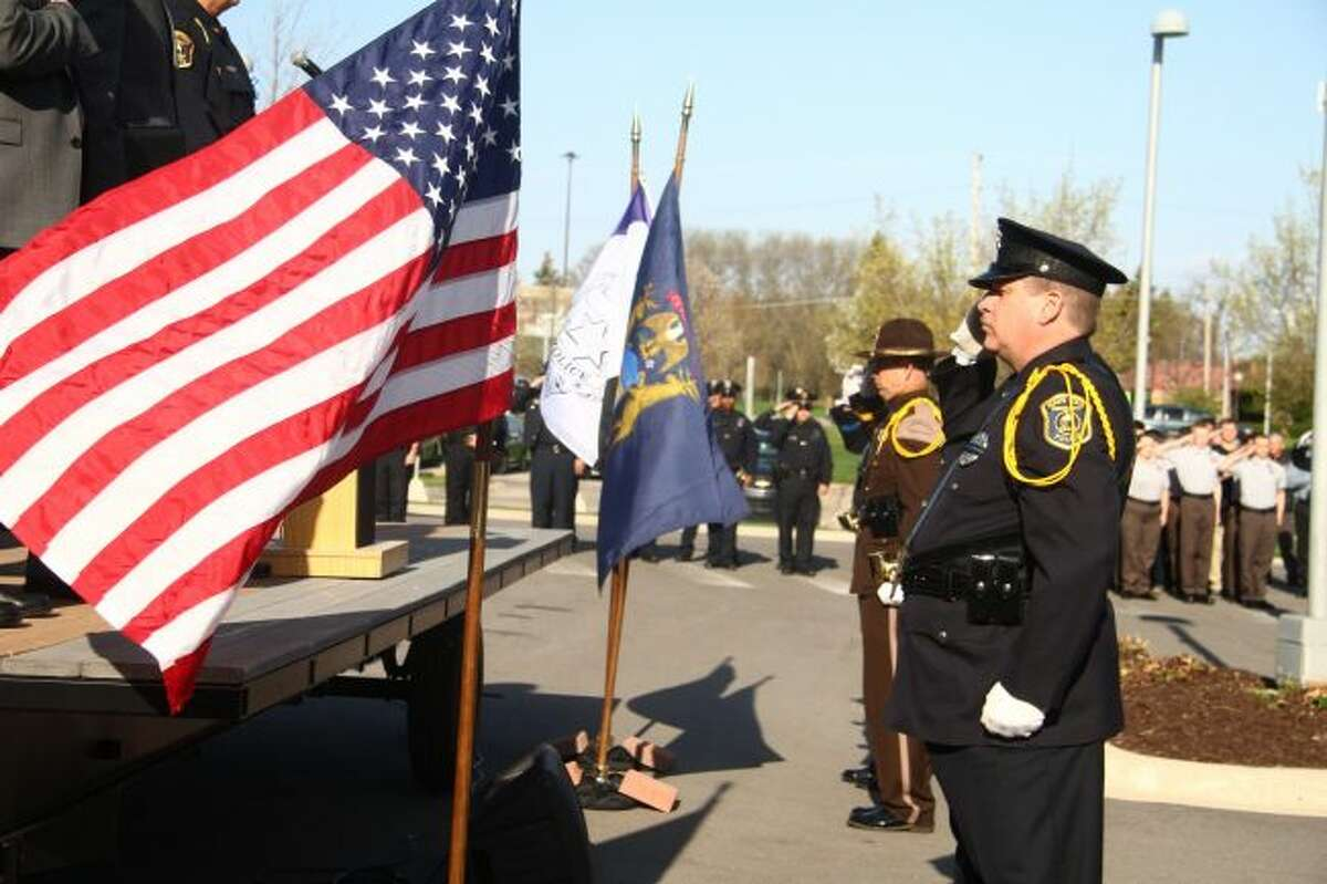 Members of the honor guard salute the flags after placing them within stands at the beginning of the Police Memorial Ceremony. (Pioneer photos/Emily Grove)