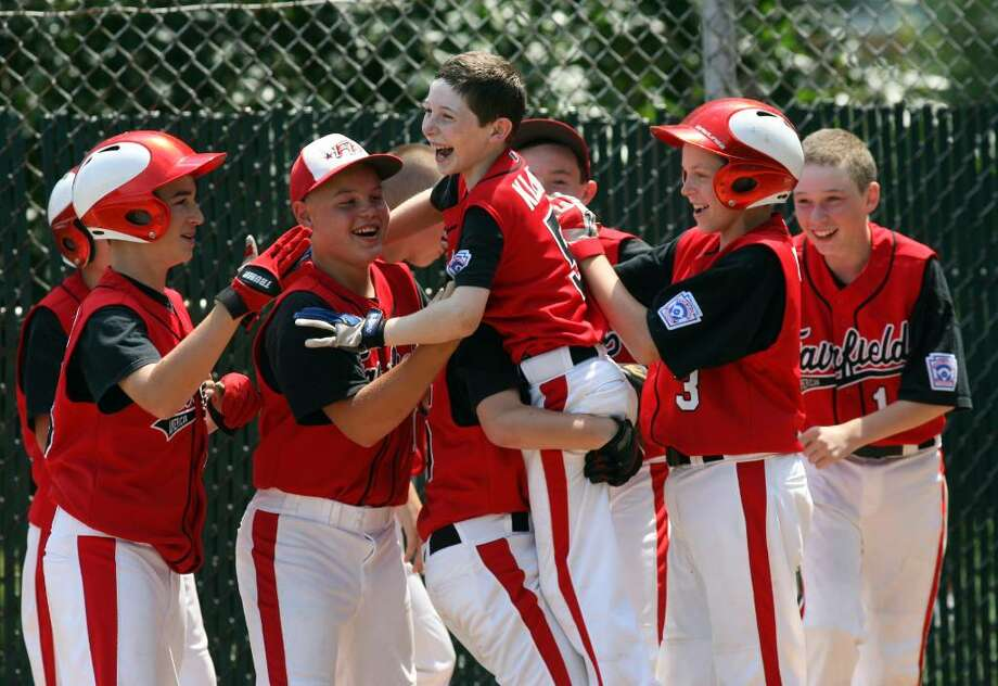 Fairfield American celebrates Nate Klein's , 5, center, game winning home run during the Connecticut State Little League championship game at Thorme field in Bridgeport on Sunday, August 1 , 2010. Fairfield advances to the New England Regional Tournament in Bristol on Friday. Photo: B.K. Angeletti / Connecticut Post