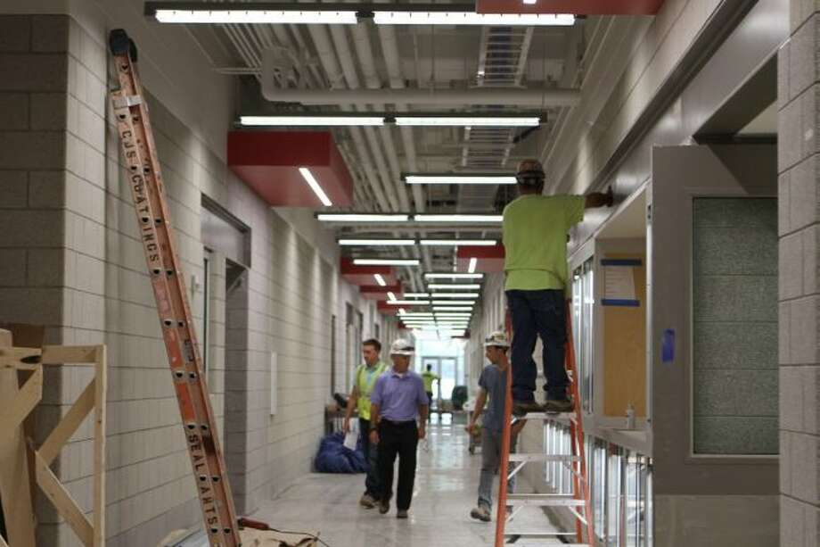 Workers walk through the Swan Technical Arts Building Annex on Ferris State University's campus and make note of some of the final touch-ups of the $30-million renovation and expansion project before students return to classes in the building for the 2018-19 academic year. (Pioneer photos/Meghan Gunther-Haas)