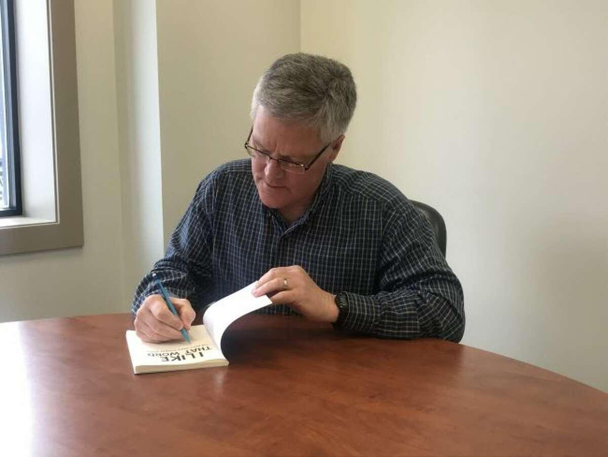 Bob Eastley signs a copy of his book