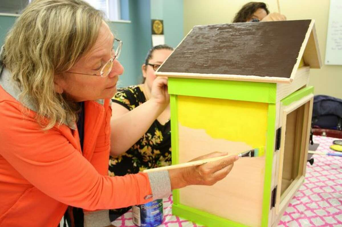 Cheryl Courtney helps paint a Little Phelps Free Library as part of the Artworks painting team. (Pioneer photo/Candy Allan)