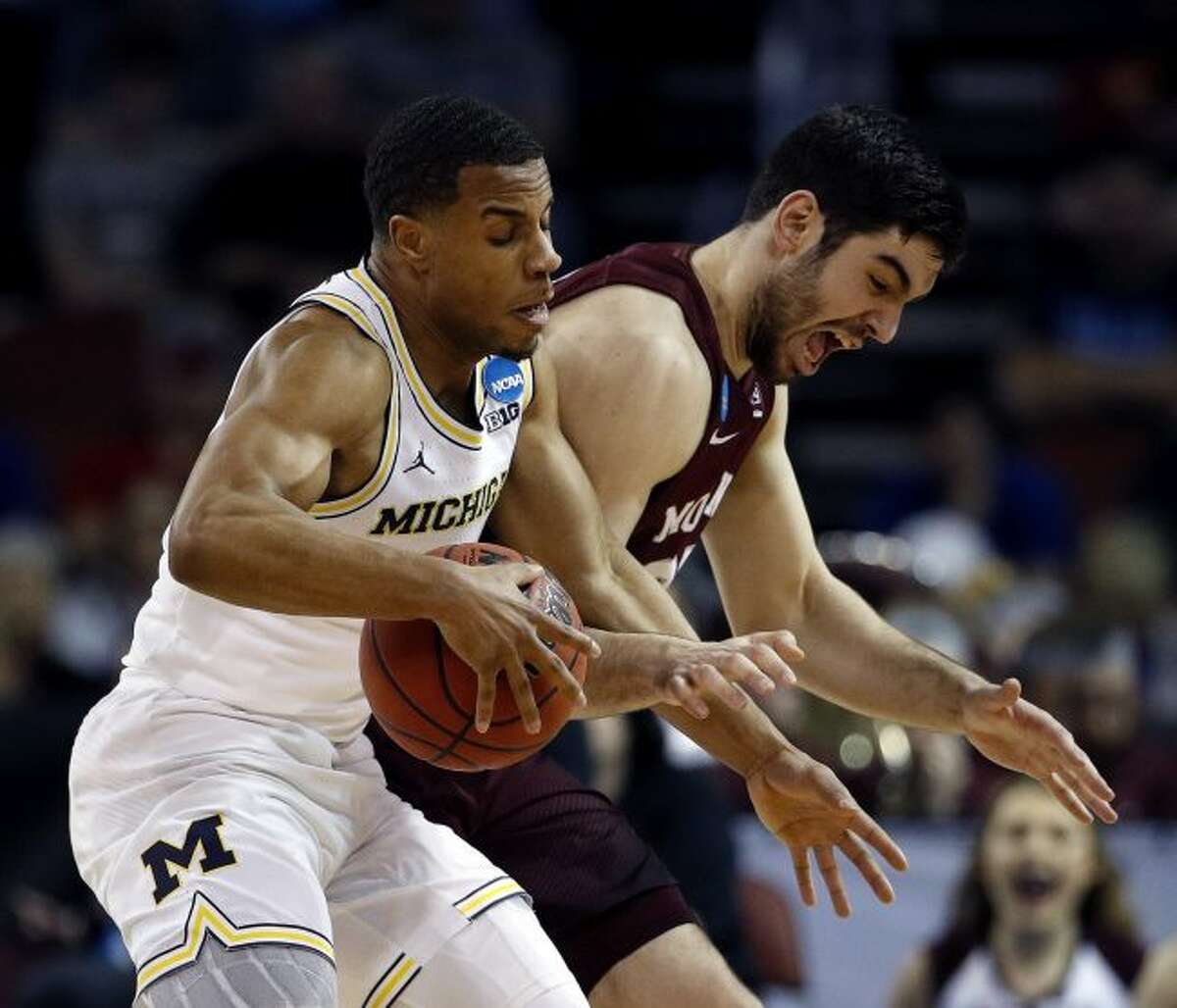 Montana forward Fabijan Krslovic, right, tries to steal the ball from Michigan guard Jaaron Simmons, left, during the first half of an NCAA men's college basketball tournament first-round game Thursday, March 15, 2018, in Wichita, Kan. (AP Photo/Charlie Riedel)
