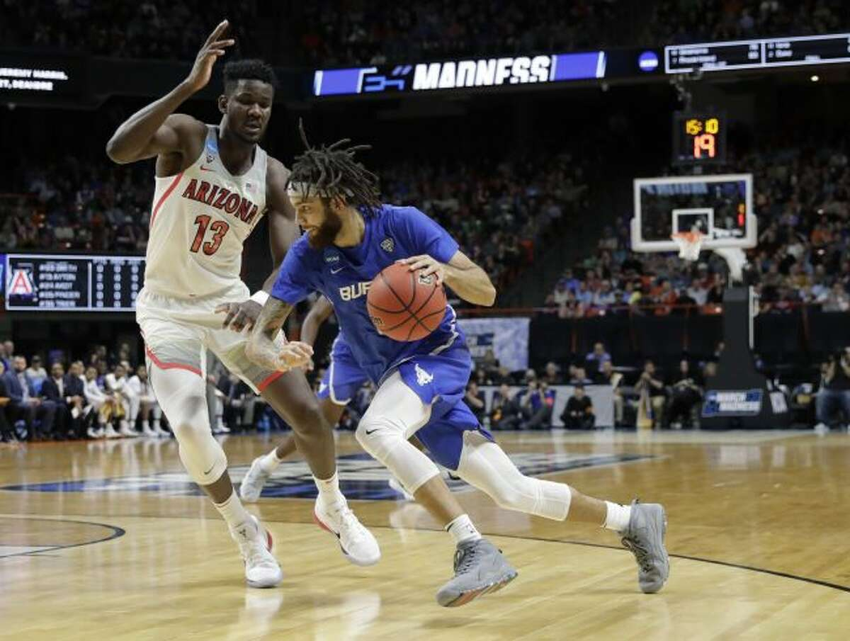 Buffalo forward Ikenna Smart (34) looks to pass around Arizona center Dusan Ristic (14) during the first half of a first-round game in the NCAA men's college basketball tournament Thursday, March 15, 2018, in Boise, Idaho. (AP Photo/Ted S. Warren)