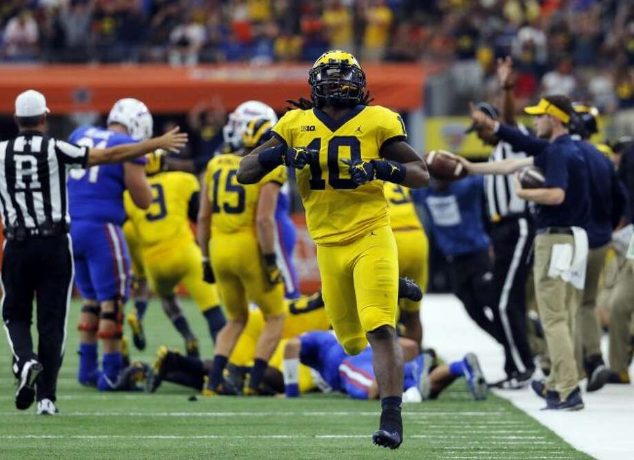 In this Saturday, Sept. 2, 2017, file photo, Michigan linebacker Devin Bush (10) celebrates a Florida turnover during an NCAA college football game, in Arlington, Texas. Bush was selected to the AP Preseason All-America team, Tuesday, Aug. 21, 2018. (AP Photo/Tony Gutierrez, File)