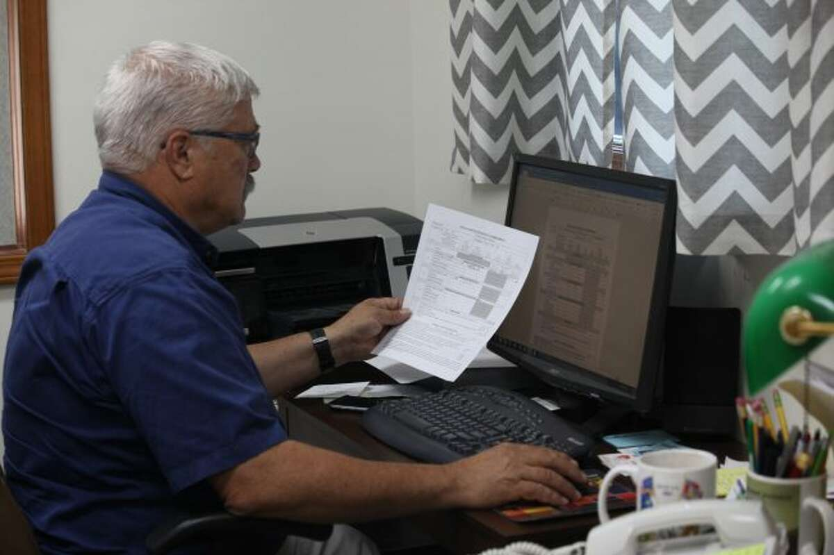 Green Charter Township Supervisor Jim Chapman works on preparing an initial response to a Freedom of Information Act (FOIA) request from a New York-based company for information relating to the 2016 presidential election. Green Township is one of many local units of government throughout Michigan to receive this FOIA request. (Pioneer photo/Taylor Fussman)