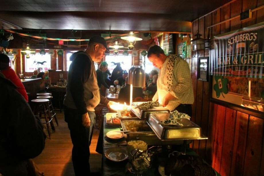 A customer lines up to get his serving of the St. Patrick's Day buffet at Schuberg's Bar and Grill. (Pioneer photos/Emily Grove)