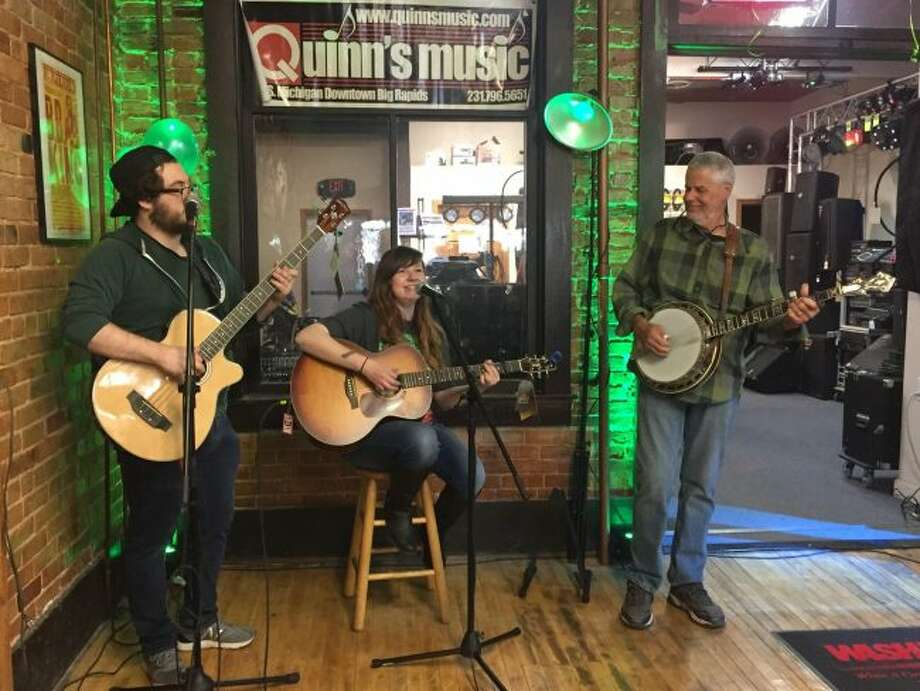"""Jake Trethaway, Allison LeVeque and Marc Conleyplay the song """"Wagon Wheel"""" during a performance in the open mic corner during the anniversary celebration at Quinn's Music on Saturday in downtown Big Rapids. The event was in honor of the store's 50th anniversary. (Pioneer photos/Emily Grove)"""