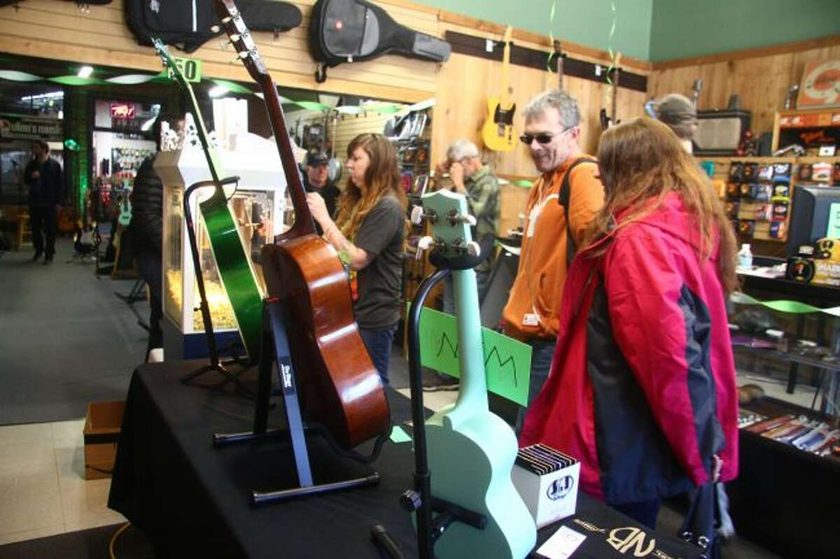 Customers look at instruments and other prizes as part of a giveaway for the 50th anniversary event at Quinn's Music.