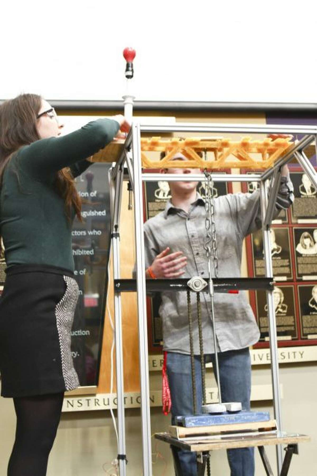 MAKING ADJUSTMENTS: (From left) Zofia Freiberg and Ryan Cosper, of the Big Rapids High School team Campanella Captains, adjust their bridge for another round of weight testing during the 18th annual Spaghetti Bridge competition at Ferris State University. (Pioneer photos/Meghan Haas)