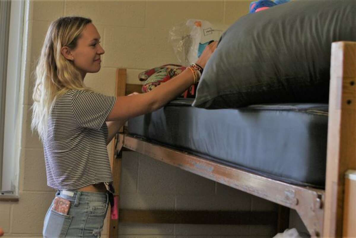 Cassidy Juntunen drops off a few items in her new dorm before heading downstairs to unload more boxes during Ferris State University's move-in day on Friday. Juntunen, along with Payton Castelaz spent the morning hours carrying the essentials for dorm life up to the room and rearranging. (Pioneer photos/Meghan Gunther-Haas)
