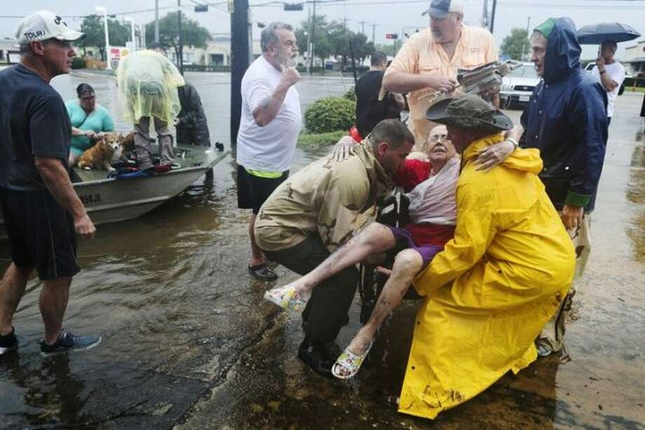 Residents of a Houston area inundated by Hurricane Harvey, rescue a neighbor. (Photo by Steve Gonzales / Houston Chronicle)