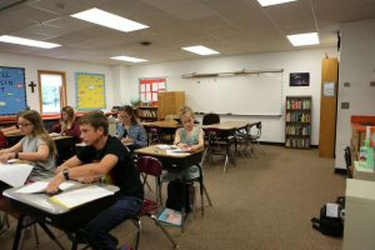Seventh- and eighth-grade students learn about an upcoming assignment and take notes during their first day back to school at St. Peter's Lutheran School.