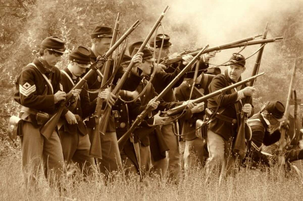 A line of re-enactors with the Tenth Michigan Infantry readies their weapons during an event. (Courtesy photo)