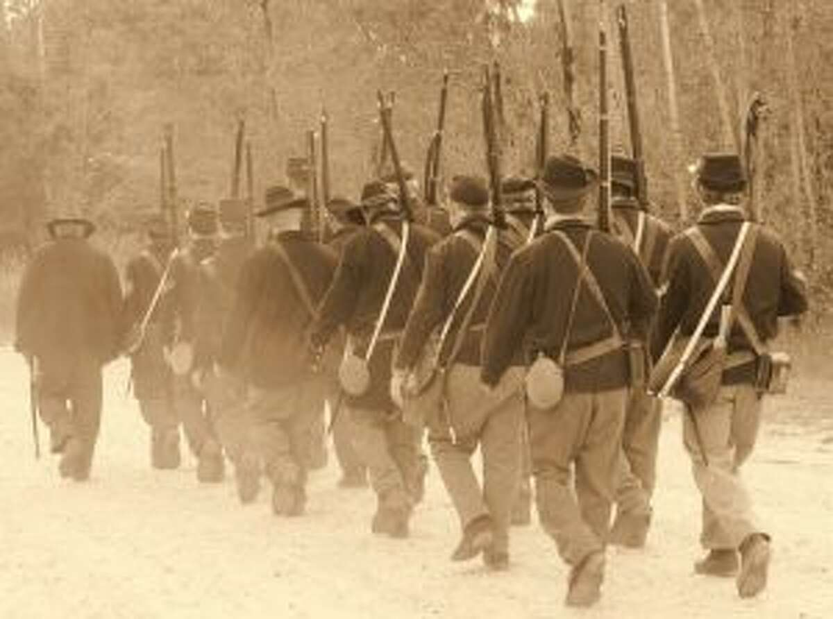 A group of Civil War re-enactors with the Tenth Michigan Infantry marches in a column formation. (Courtesy photo)