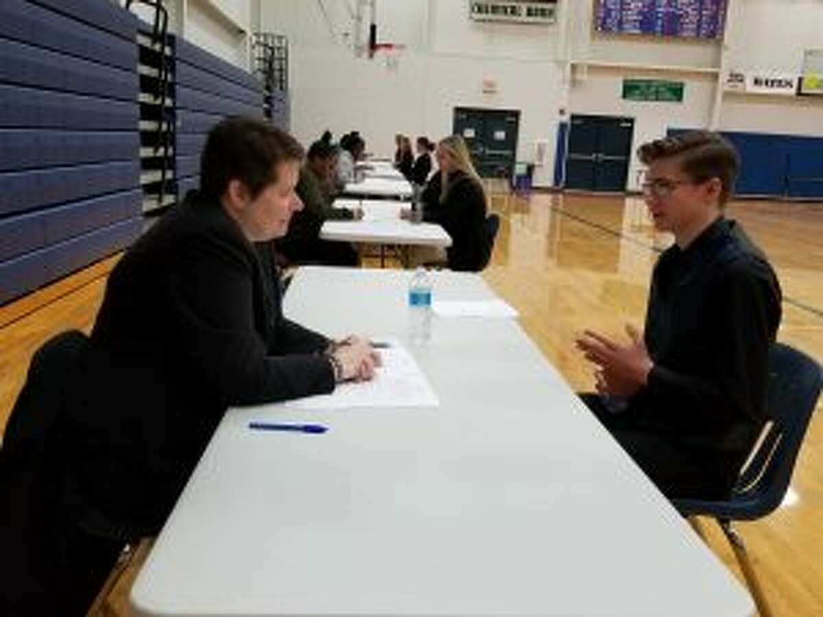 (From left) Sara Keineth, of the Michigan State University-Extension office, talks with Crossroads Charter Academy student Alex Withers about his school and career goals during mock interview day on Tuesday.