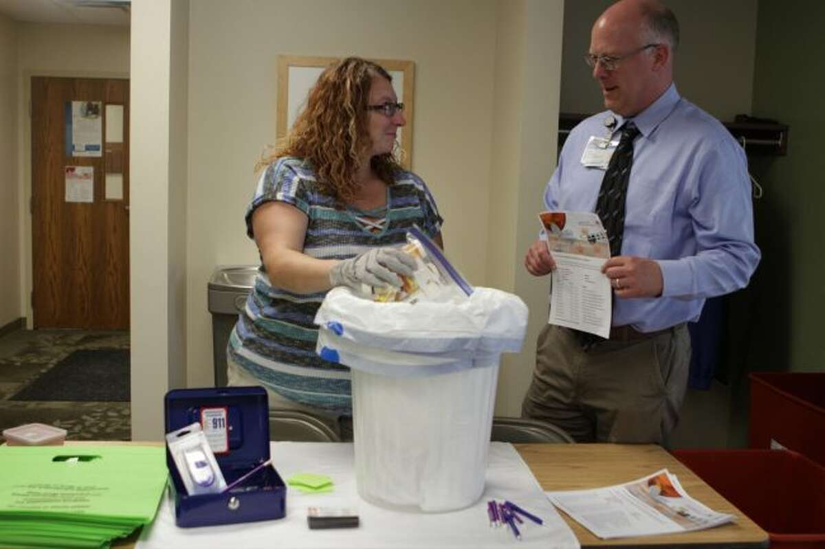 During Tuesday's medication and needle take-back event in Evart, (from left) Shay Tullar, Ten16 Recovery Network prevention coordinator, and Scott Lombard, community outreach manager for Spectrum Health Big Rapids and Reed City hospitals, discuss upcoming take-back dates set through the rest of this year at different locations in Mecosta and Osceola counties. (Pioneer photos/Meghan Gunther-Haas)