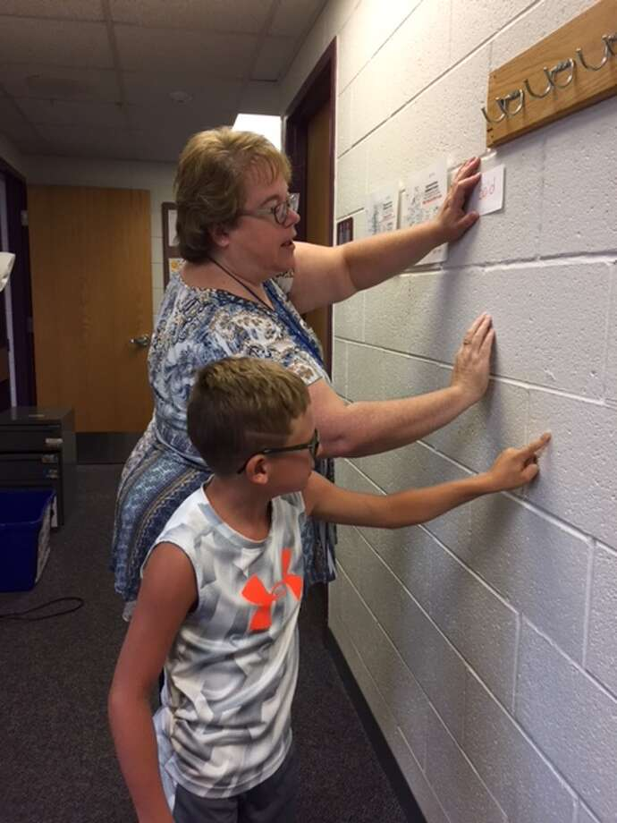 Aiden Bull (front), son of Josh and Katie Bull, of Big Rapids, working with his tutor, Lori Weller, SLD Read education services manager. (Courtesy photo)