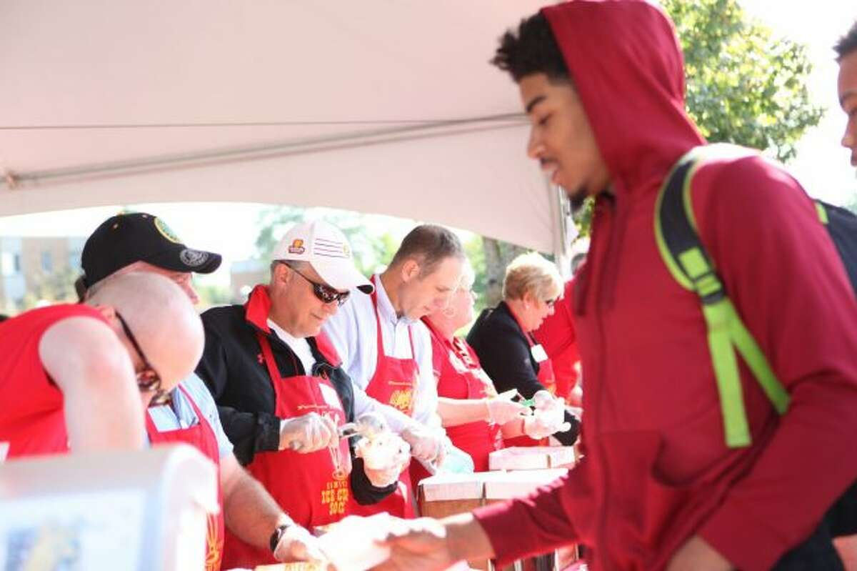 Ferris State University and City of Big Rapids officials scoop out ice cream during the Founders' Day celebration on Thursday, Aug. 31. (Pioneer photos/Meghan Haas)
