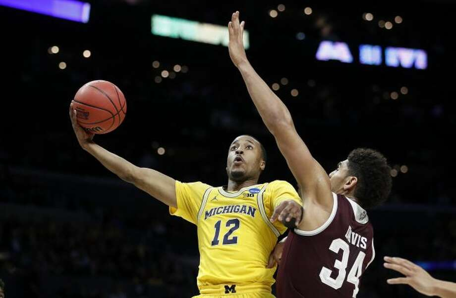 Michigan guard Muhammad-Ali Abdur-Rahkman (12) shoots as Texas A&M center Tyler Davis (34) defends during the first half ofthe game on March 22, 2018, in Los Angeles. (AP Photo/Jae Hong)