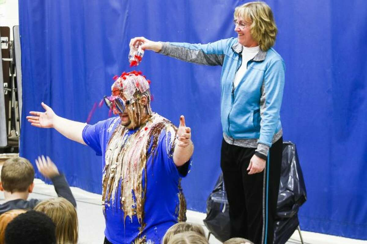 FINISHING TOUCH: Secretary Peggy Borders puts the final topping on Mecosta Elementary Principal Kyle Talicska's head, dumping a jar of cherries on him.
