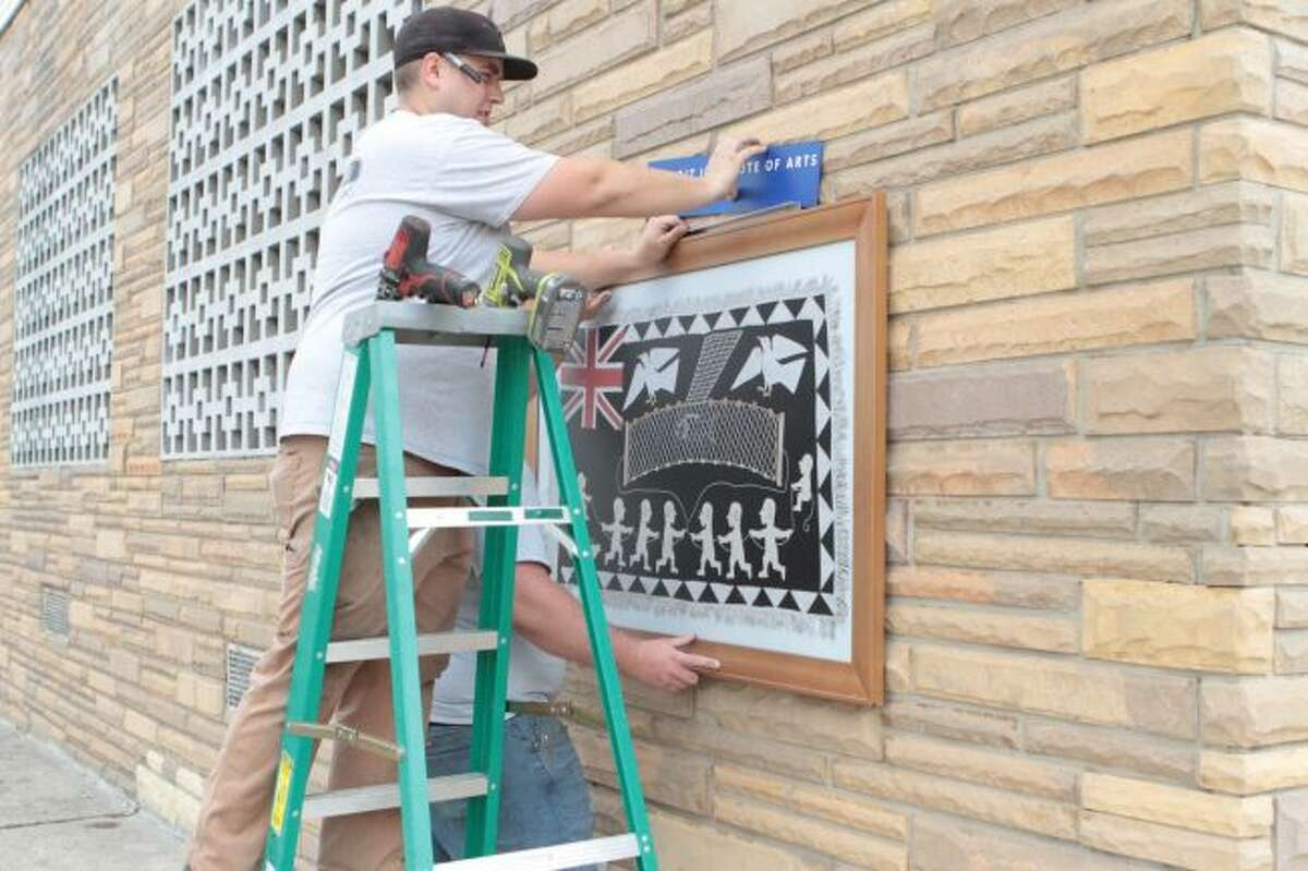 Frank Dutchak (front) and Donny Stokes, with LaVanway Sign Company, help hang a piece of art for the Detroit Institute of Arts' Inside Out program in downtown Big Rapids. As part of the program, there will be 15 high-quality reproductions of famous pieces of art on display throughout town for the next several months, with programming and events for the project to be announced soon. (Pioneer photo/Taylor Fussman)