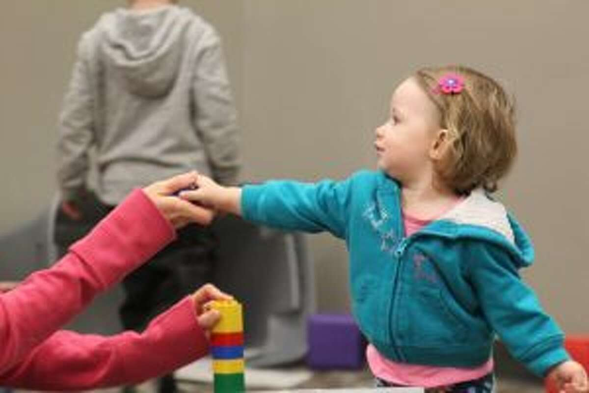 BUILDING: Rilee Grzybowski spends time gathering blocks during Thursday's Community Play Group.
